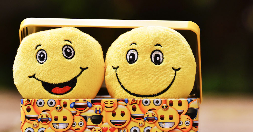 Smiley plush toys inside a box covered by happy faces emojis
