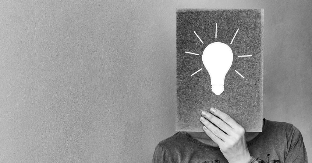 woman holding an idea icon on a board over her face